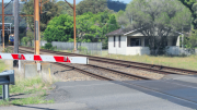 A northbound train approaches the level crossing at Woy Woy