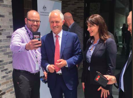 Prime Minister Turnbull and Member for Robertson, Ms Lucy Wicks, pose for a photograph with an ATO employee