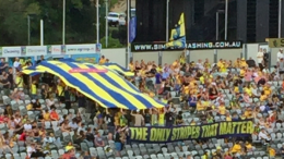 Fans hold up a giant Mariners Shirt at the traditional NYE game in Gosford.