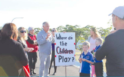 Mr Bill Symington, holding the plackard, speaking with Gwandalan residents about the park