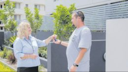 Lynn Freeland, of Pacific Link, hands over the keys to a tenant's new home